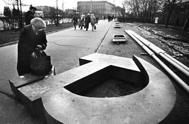 Женщина ищет что-то в сумке на поваленном серпе и молоте, Москве, 1991 год.