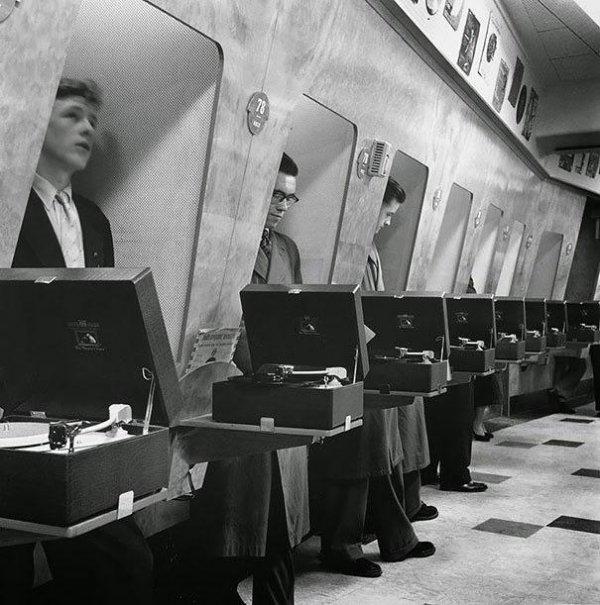 Посетители музыкальных магазинов прослушивают пластинки в специальных «примерочных». Лондон, 1955 год