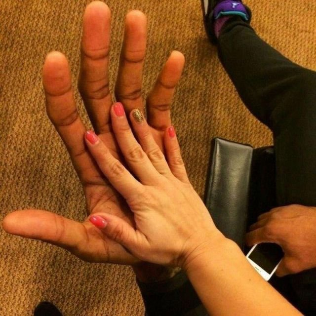 Рука девушки в ладони баскетболиста Кавая Леонарда