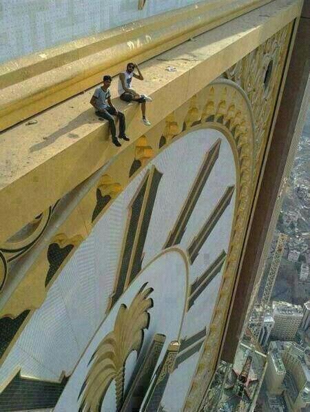 Два человека сидят на часовой башне Абрадж аль-Бейт в Мекке
