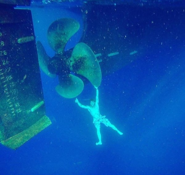 Пловец, держащийся за гигантский гребной винт подводной лодки