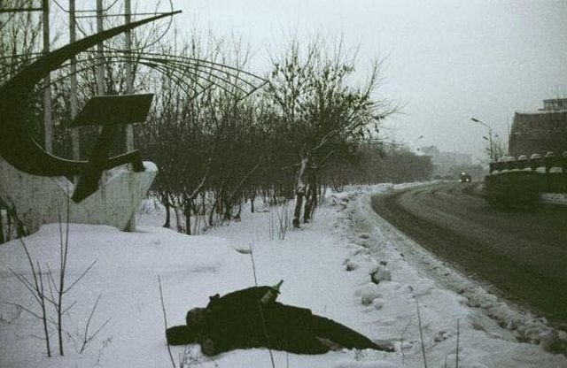 Уставший от употребления портвейна мужчина, лежит на обочине зимней дороги. Новокузнецк, 1994 год.