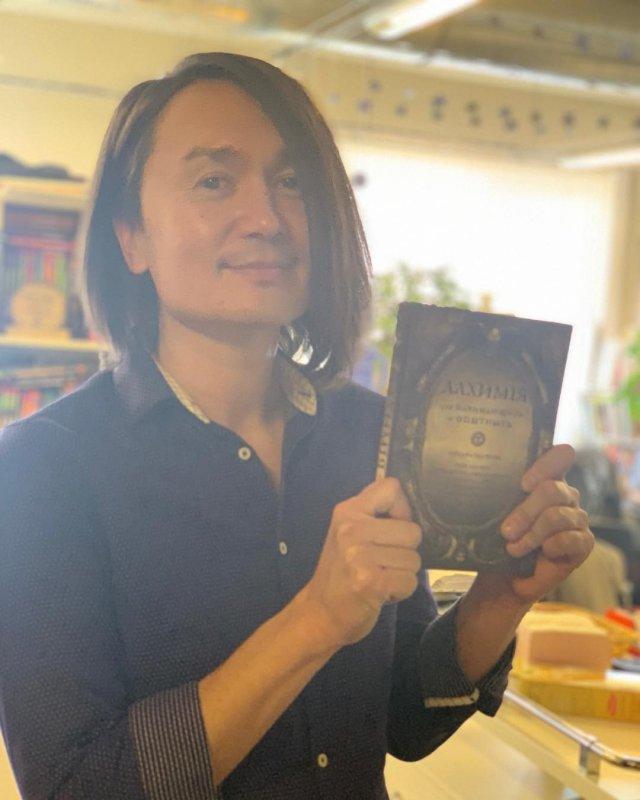 Экстрасенс и шаман Дардо Кусто в черной рубашке с книгой