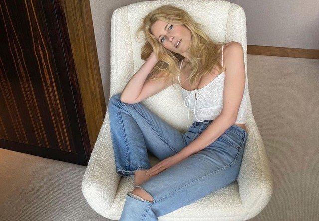 Топ-модель Клаудия Шиффер в белой блузке и синих джинсах