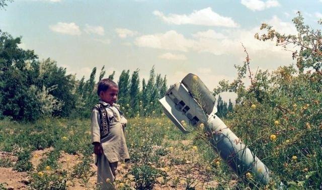 Афганский мальчик, наблюдающий за неразорвавшейся бомбой