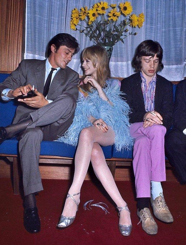 Ален Делон весело общается с Марианной Фейтфулл, девушкой Мика Джаггера, а тот грустно сидит рядом, 1968 год