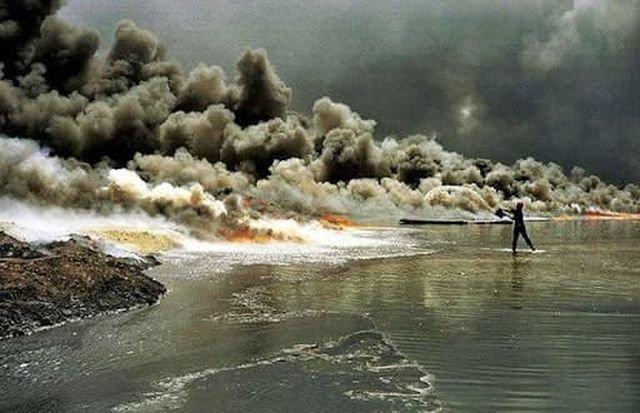 Человек с ведром пытается потушить подожженную разлитую нефть. Война в Персидском заливе, 1991 год.