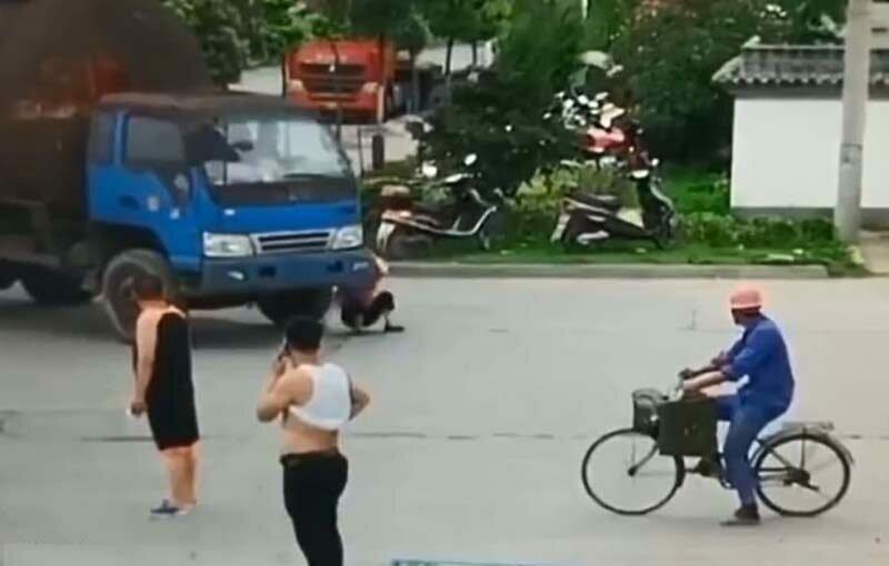 Камера наблюдения засняла мошенницу, которая бросилась под колеса грузовика (2 фото + видео)