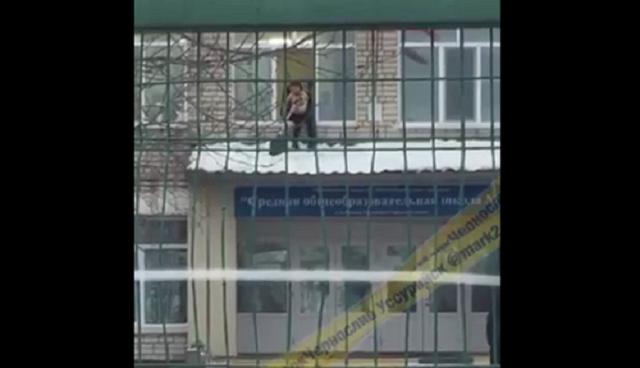 В Уссурийске заметили, как полураздетый школьник убирает снег с козырька школы