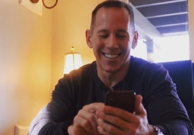 Джефф Гебхарт в темном свитере смотрит на экран смартфона
