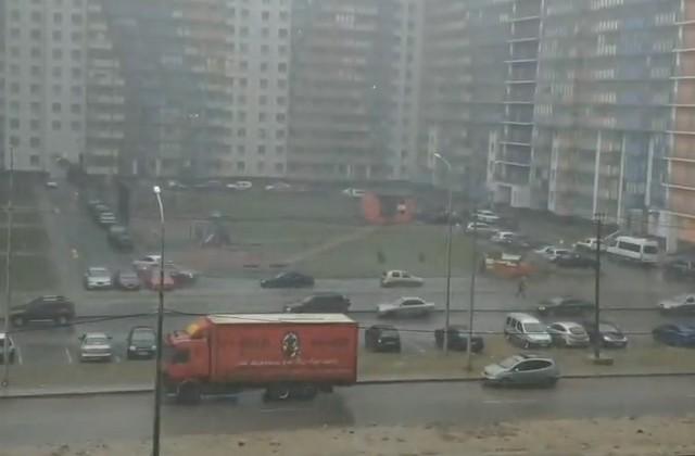 Оранжевый грузовик припаркован у обочины на фоне жилых домов