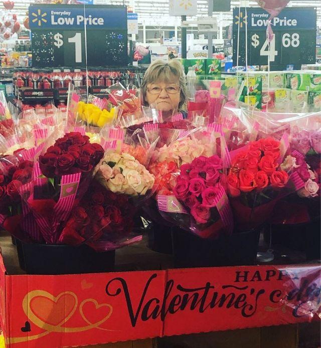 Сотрудница магазина на фоне цветов