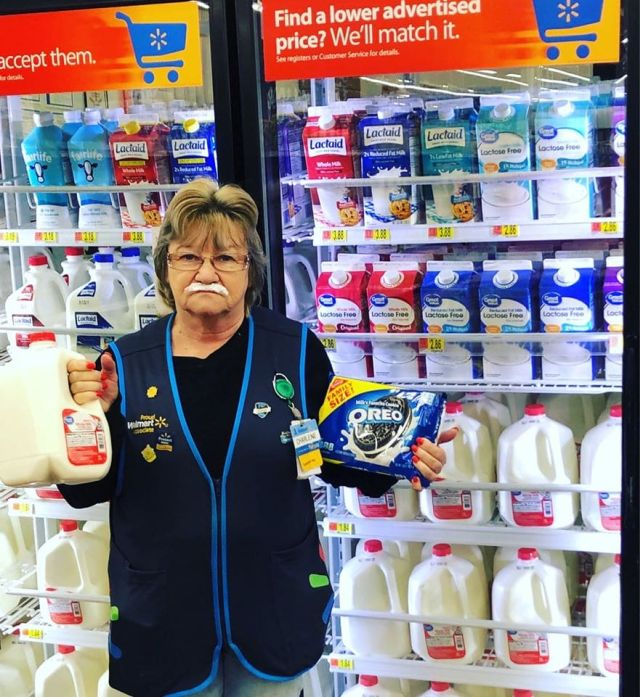 Сотрудница магазина на фоне молочных продуктов