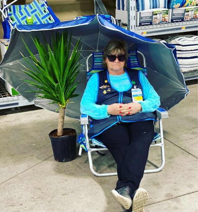 Сотрудница магазина под зонтиком в раскладном кресле