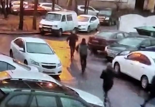 Петербургский двор, в котором припаркованы машины и бегут люди