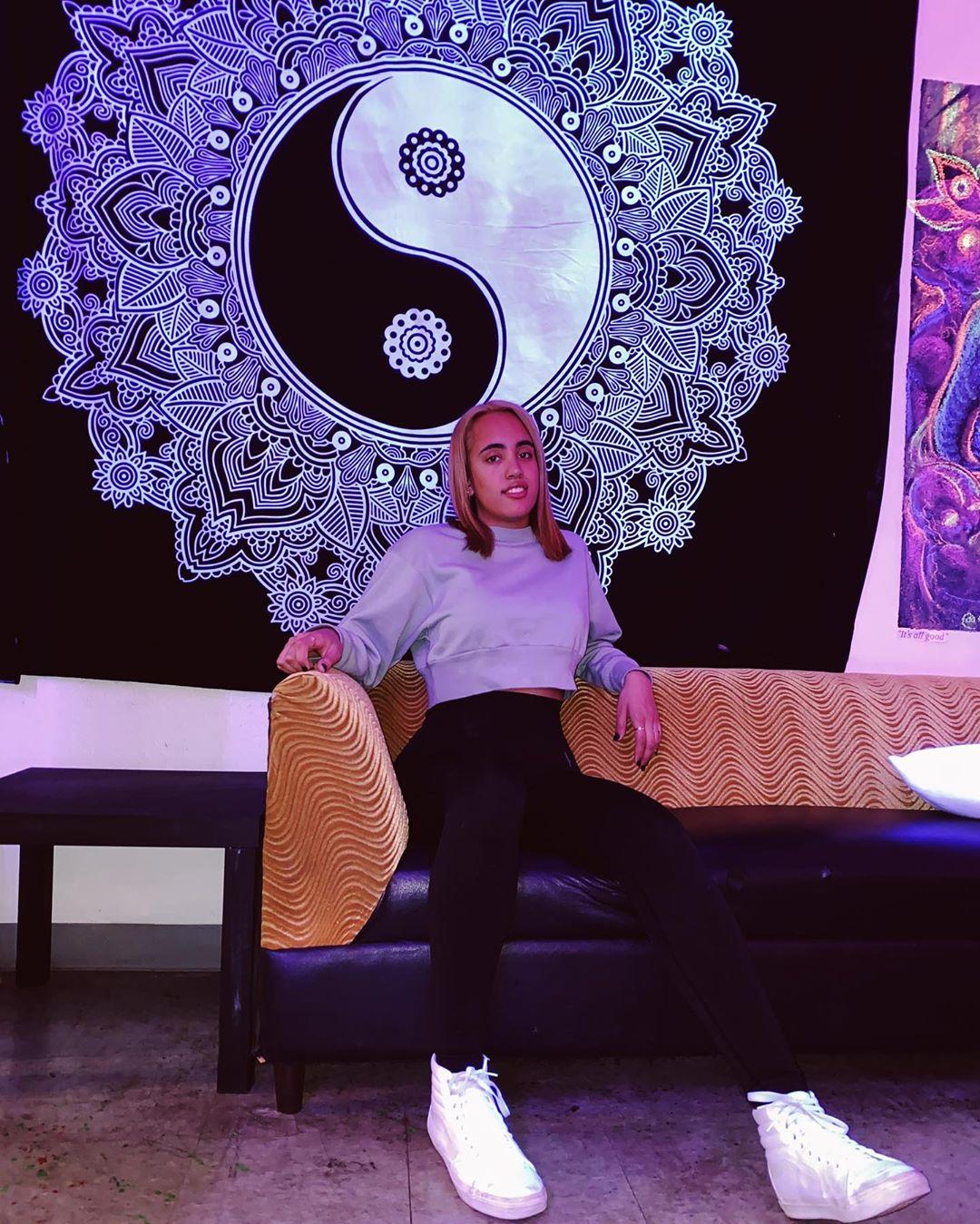 Симона Джонсон сидит на бежевом диване сзади символ инь-янь