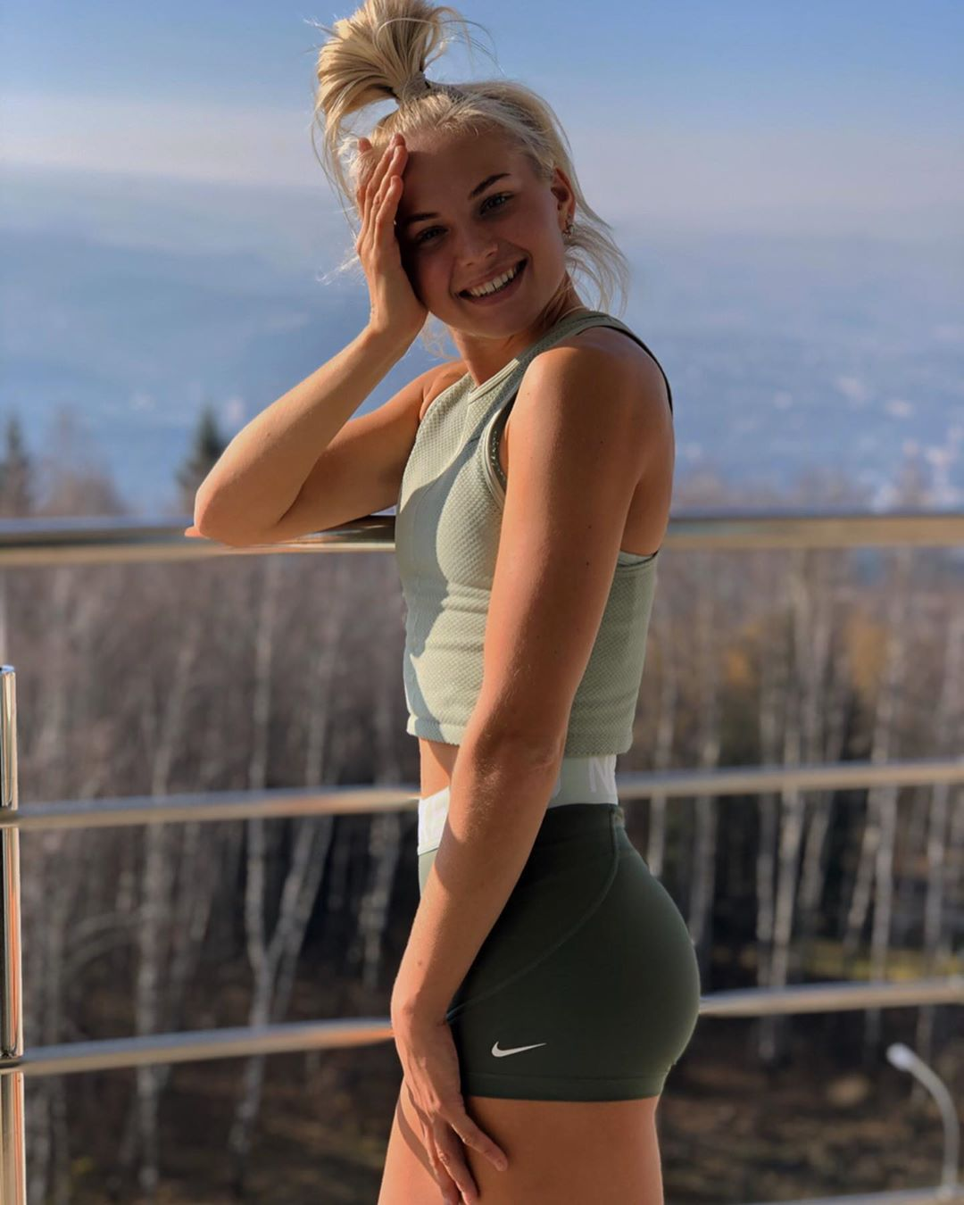 Ксения Трибунова на балконе в серой кофте и черных спортивных шортах