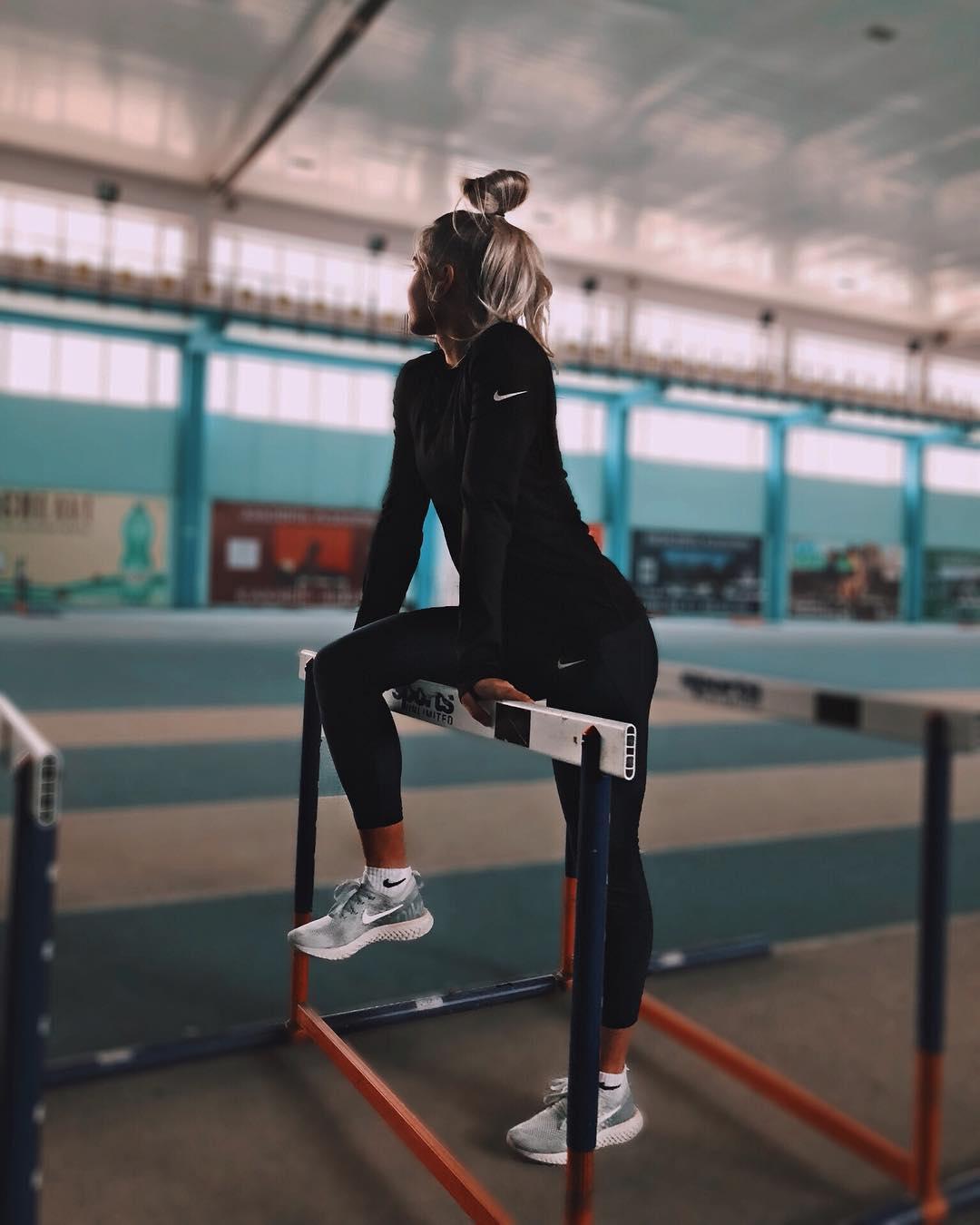 Ксения Трибунова в черном костюме в легкоатлетическом зале