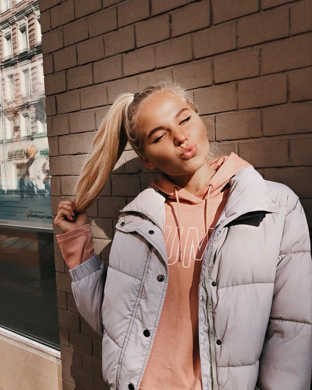 Ксения Трибунова на фоне кирпичной стены в серой куртке и розовой кофте