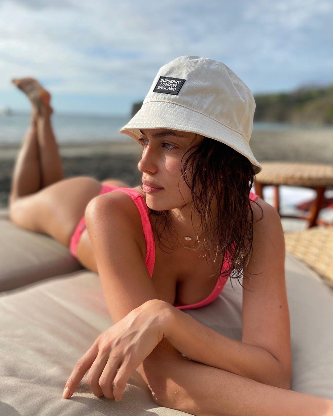 Ирина Шейк загорает на пляже в розовом купальнике и светлой панаме