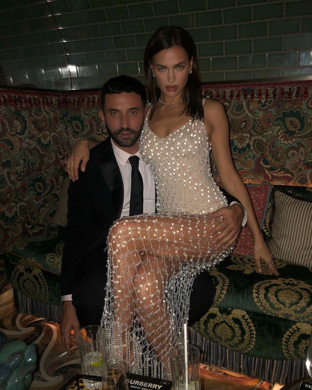 Ирина Шейк в белом платье с блестками сидит на коленях у мужчины