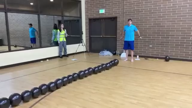 Мужчина лопает воздушные шары ногами