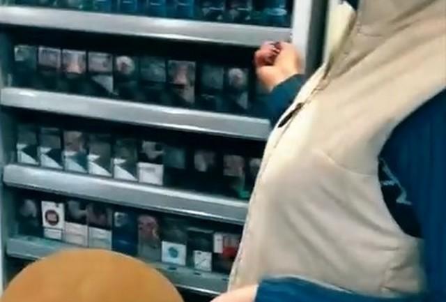 Продавщица за прилавком показывает покупателю сигареты