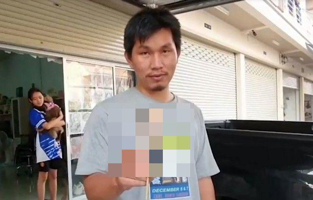 Суттирак Хайлим в серой футболке стоит на улице и держит в правой руке еду