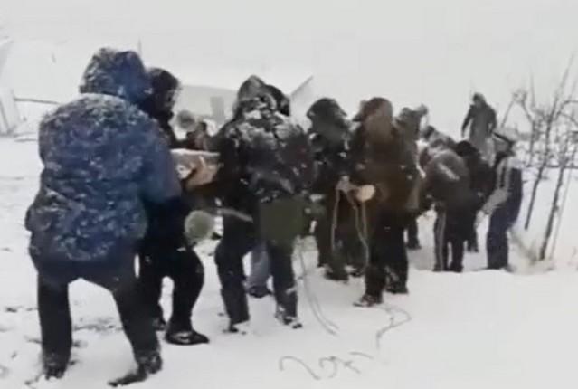 Мужчины поднимают столб на фоне снега