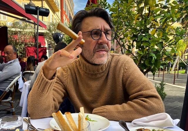 Сергей Шнуров в коричневом свитере сидит на улице и ест сырную палочку