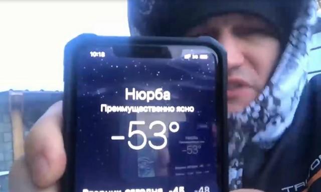 Мужчина показывает температуру воздуха в Якутии на iPhone