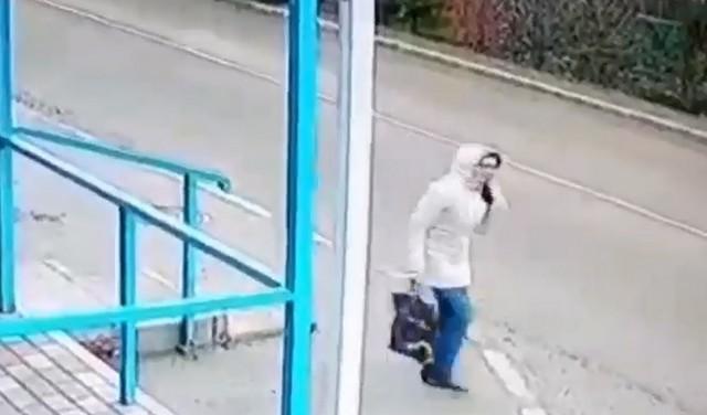 Женщина в белой куртке стоит на остановке