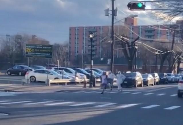 Парень бежит по улице от людей в защитных медицинских костюмах