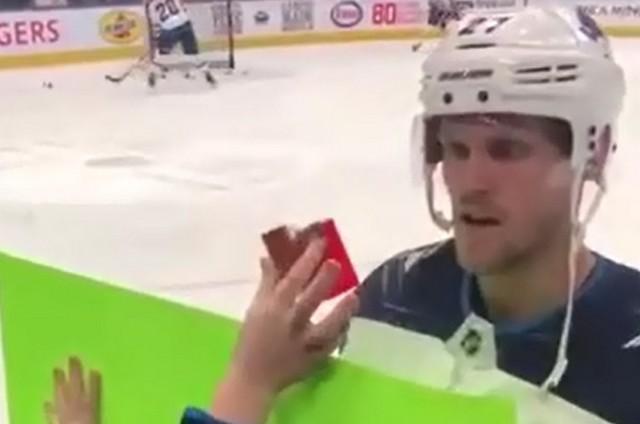 Хоккеист смотрит через защитное стекло на руку мальчика