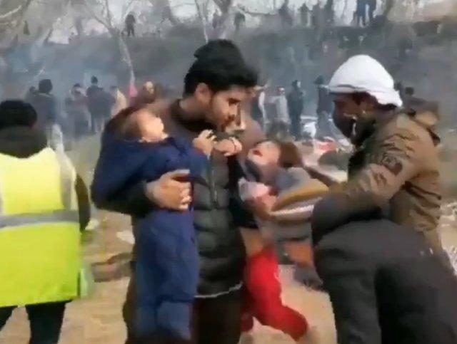 Беженцы на границе Греции держат детей над костром