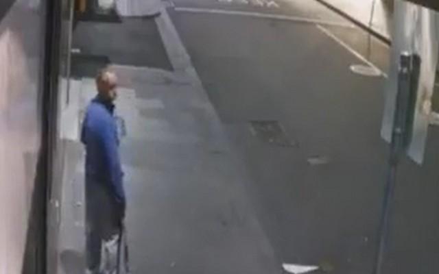 Мужчина в синем свитере стоит на улице