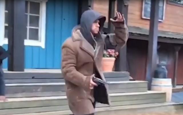 Мужчина идет в коричневой куртке, синем капюшоне и пистолетом