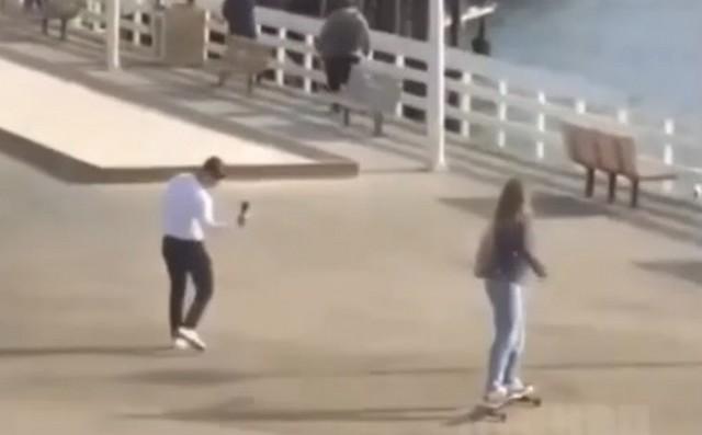 Молодой человек снимает девушку на скейте на пляже