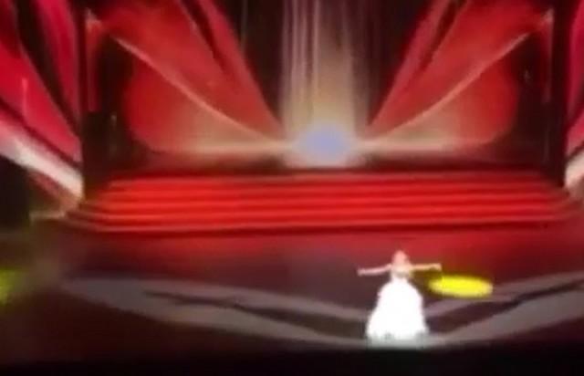 Певица стоит на сцене на фоне красного экрана