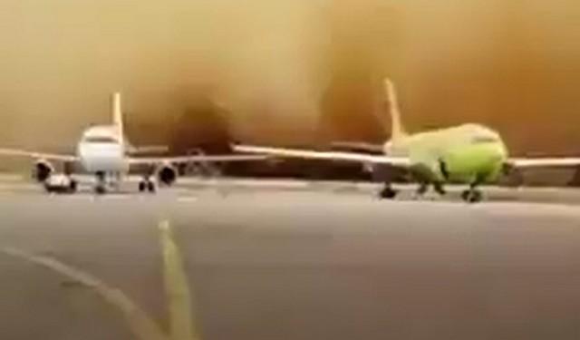 Самолеты стоят в аэропорту, а сзади надвигается песчаная буря
