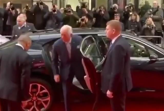 Принц Чарльз в черном костюме выходит из автомобиля в окружении охранников