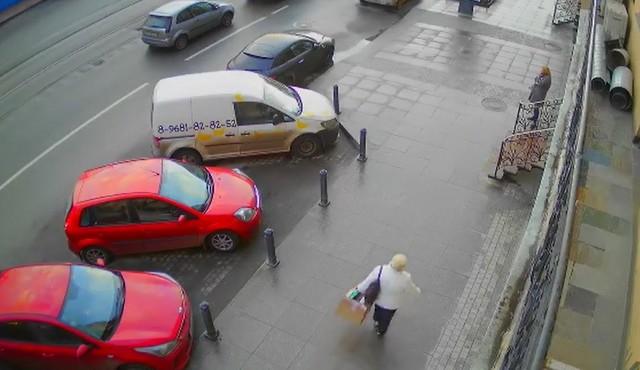 Автомобили припаркованы около тротуара, по которому идут люди