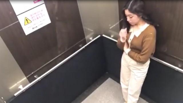 Кореянка едет в лифте - в белых штанах и кориченой кофте