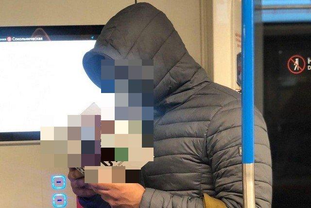 Мужчина в метро в противогазе и с книгой