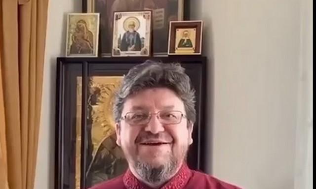 Священник на фоне икон