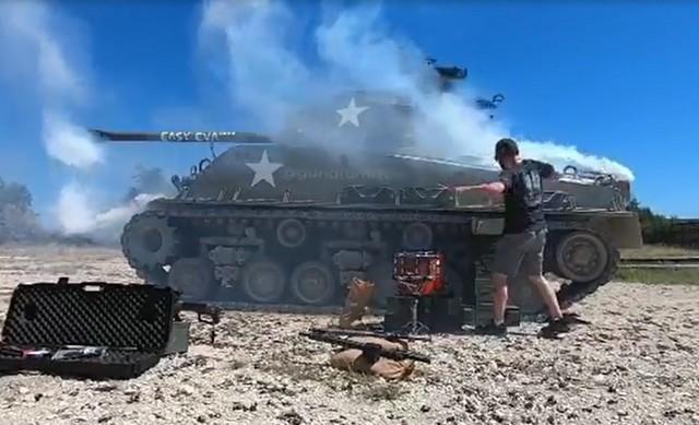 Музыкант играет на фоне танка