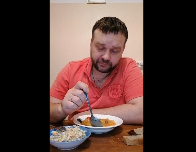 Мужчина обедает за столом