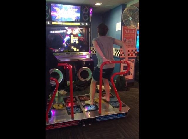Парень играет на танцевальном автомате