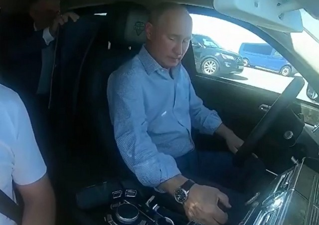 Владимир Путин за рулем в синей рубашке