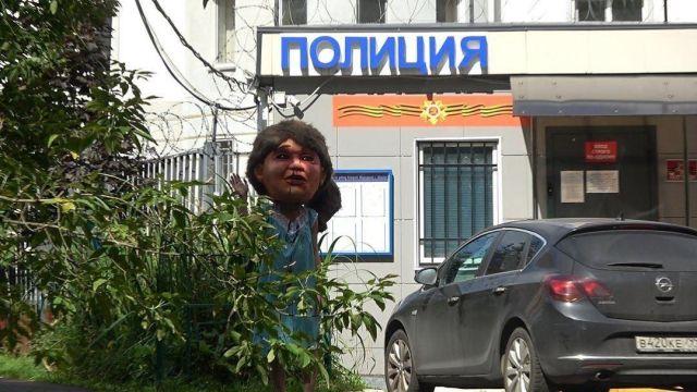Активистка в костюме с накладной головой машет рукой